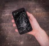 Hand holding a mobile phone with a broken screen — Stock Photo
