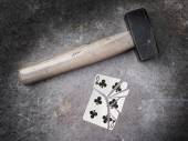 Hammer with a broken card, six of clubs — Stock Photo