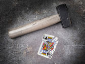 Hammer with a broken card, king of clubs — Stock Photo