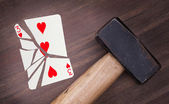 Hammer with a broken card, three of hearts — Stock Photo