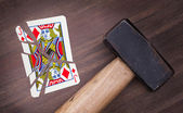 Hammer with a broken card, jack of diamonds — Stock Photo