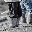 Concrete workers in heavy boots working in new wet concrete. — Stock Photo #62747715