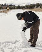 Man bygga en snögubbe — Stockfoto