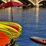 Постер, плакат: Kayaks Stacked on Dock in Water