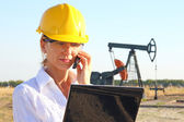 Business woman in an oilfield talking on cell phone — Foto Stock