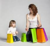 Little girl and her mother with shopping bags — Stok fotoğraf