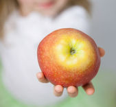 Hand of child holding ripe apple — Stock Photo