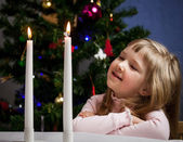 Pretty little girl looking on fire of candles — Stock Photo