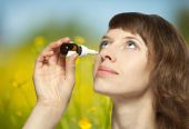 Woman dropping a rhinitis medicine — Stock Photo