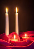 Beautiful candles on red cloth  — Stock Photo
