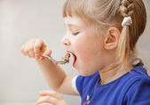 Adorable baby girl eating porridge — Stock Photo
