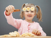 Little girl cutting a ripe banana — Stock Photo