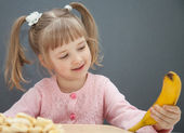 Little girl holding a ripe banana — Stock Photo