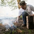 Young man lighting a campfire — Stock Photo #64765341