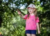 Pretty little girl holding brushwood — Stock Photo
