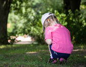 Little girl  gathering something in grass — Stock Photo
