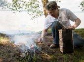 Young man lighting a campfire — Stok fotoğraf