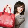Beautiful young woman holding red bag — Stock Photo #68352989