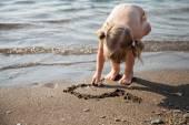 Little girl drawing on sand — Stok fotoğraf