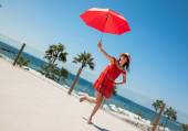 Woman in red sundress with umbrella — Stock Photo