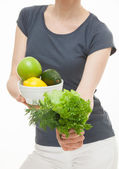 Woman holding greens and fruits — Stock Photo