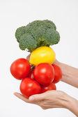 Hand holding tomatoes, broccoli and lemon — Stock Photo