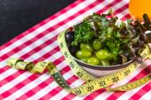 Diet green salad and measuring tape slimming  — Stock Photo