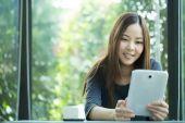 Junge asiatische Mädchen Verwendung Tablet Suche Informationen — Stockfoto