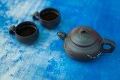 Escuro jogo de chá em fundo azul — Fotografia Stock