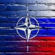 Nato and Russia Flag painted on brick wall — Stock Photo #53771275
