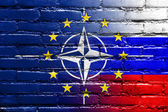 Nato, EU and Russia Flag painted on brick wall — Stock Photo