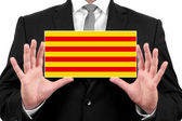 Businessman holding a business card with Catalonia Flag — Stock Photo