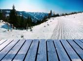 Wooden balcony on winter landscape with skiing path — Stock Photo