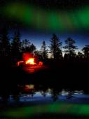 Fire burning at night in a forest with northern lights — Stock Photo