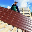 Worker puts the metal tiles on the roof — Stock Photo #54313521