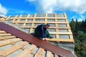 Worker puts the metal tiles on the roof — Stock Photo