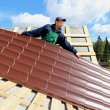 Worker puts the metal tiles on the roof of a wooden house — Stock Photo #55394263