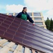 Worker puts the metal tiles on the roof of a wooden house — Stock Photo #55394313
