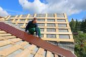 Worker puts the metal tiles on the roof of a wooden house — Stock Photo