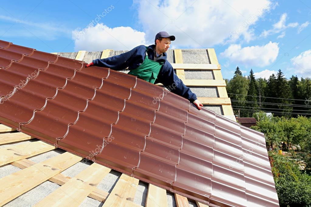 Trabajador pone las tejas met licas en el techo de una for Tejas livianas para techos