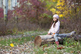 Girl sitting on a log in the woods — Stock Photo