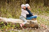 Two Beautiful girls wearing a beret sitting on log posing — Stock Photo