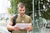 Portrait of serious urban man with tablet computer in the street, modern life concept. — Stock Photo