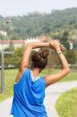 Sporty woman doing stretches before exercising in the park. — Stock Photo