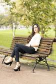 Elegant beautiful woman sitting on bench in the park. — Foto de Stock