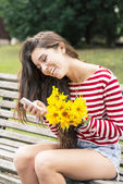 Smiling happiness woman with flowers looking message on mobile, feeling concept. — Stock Photo