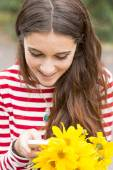 Closeup portrait of smiling happy girl with flowers looking message in phone. — Stock Photo