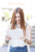 Beautiful young woman holding and looking tablet compuer in the — Foto Stock