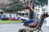 Beautiful young happiness girl sitting on bench and reading book — Stock Photo
