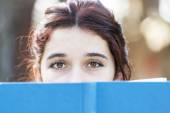 Closeup portrait of beautiful caucasian woman with blue book. — Stock Photo